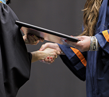 Photo: a graduate's hand receiving a diploma and shaking hands