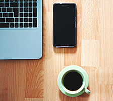 Photo: computer, phone, and coffee on a table