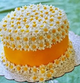 Photo: cake with orange frosting and white daisies