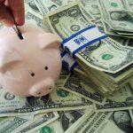 Photo: piggy bank on pile of dollar bills