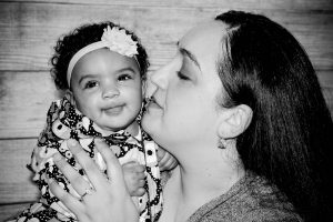 Photo: black and white photo of mother kissing her smiling baby