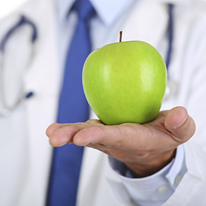Photo: Male medicine doctor hands holding green fresh ripe apple.