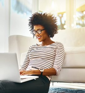 Woman sitting and smiling while using her laptop