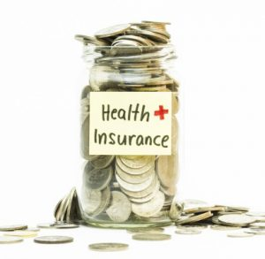 A jar filled with coins with health and insurance written on the outside