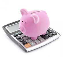 Pink piggy bank standing on a calculator