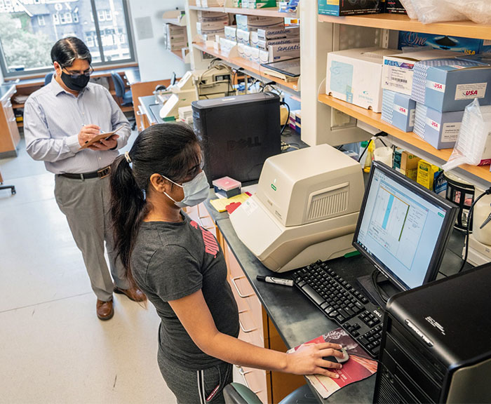 Ramesh Raina, interim vice president for research and professor of biology, and graduate student Deepjyoti Singh working in a laboratory on campus