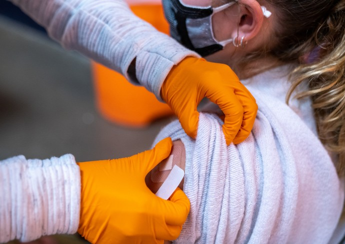 closeup of Barnes Center nurse putting a bandage on a person's arm after administering a flu shot