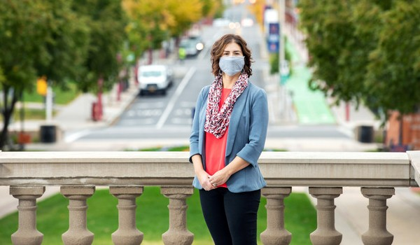 portrait of Melanie Domanico in front of the Hall of Languages in fall